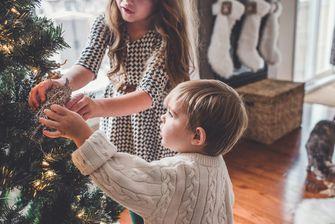Op deze foto versieren twee kinderen een kerstboom.