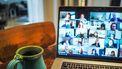 Op deze foto is een laptop te zien waarop een digitale bijeenkomst gaande is.