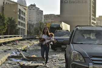 Een foto van een vrouw met haar kinderen in het puin van Beiroet