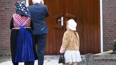 Op deze foto zijn bezoekers van de kerk in Staphorst te zien, ze lopen richting de ingang.