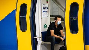 Op deze foto zie je een man in trein met een mondkapje