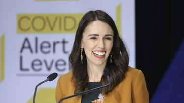 Een foto van de Nieuw-Zeelandse premier Jacinda Ardern, ze heeft een geel jasje aan en lacht breed.