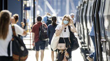 Een foto van een zonnig perron waar mensen in een trein instappen, er komt een mevrouw aanlopen die een mondkapje op heeft.