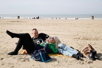 Bezoekers genieten van het aangename lenteweer op strand van Scheveningen. Foto: ANP / Bas Czerwinski