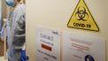 Een foto van een zorgmedewerker in beschermende kleding die een deur opend met waarschuwingen erop
