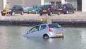 Man op het dak van een auto in het water, terwijl hij lachgas neemt.