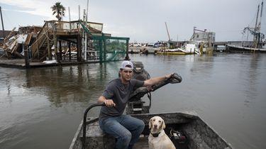 Op deze foto is een man te zien op een bootje met een hond. Ze varen langs verwoeste huizen.
