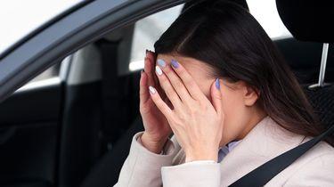 Een foto van een balende vrouw achter het stuur