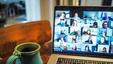 Op deze foto is een laptop te zien van iemand die met een video vergadering bezig is.