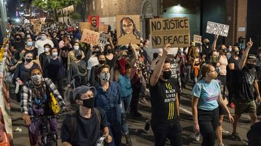 Op deze foto zijn demonstranten te zien die borden vasthouden met daarop 'no justice, no peace' en foto's van Breonna Taylor erop.