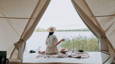 Een foto van een luxe tent waar een vrouw voor zit