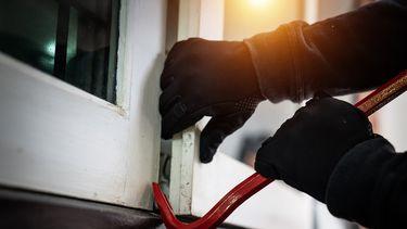 Minder inbraken: een inbreker probeert met een koevoet in te breken