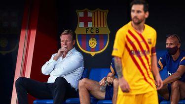 Op deze foto is Ronald Koeman te zien, tijdens een wedstrijd van Barcelona. Op de voorgrond is Messi te zien.