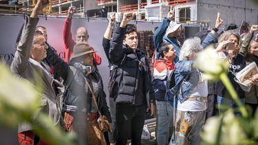 Op deze foto zie je demonstranten voor het INIT gebouw, waar het hoofdkantoor van de Volkskrant is gehuisvest. Actievoerders van onder meer Viruswaanzin protesteren bij diverse mediabedrijven omdat er volgens hen nauwelijks meer eerlijke en kritische journalistiek is.