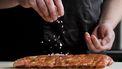 Een foto van twee handen die voedsel met zout bestrooien