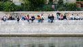 Een foto van mensen die op de hoge kade van de Seine in Parijs (Frankrijk) zitten te genieten.