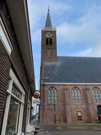 Een foto zoals vaak te zien in een dorp: kerk en kroeg bij elkaar.