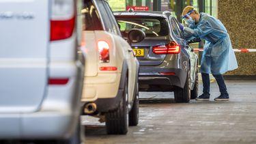 Op deze foto is een medewerker van de GGD neemt een coronatest af bij iemand in een auto.