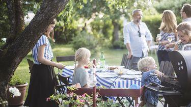 Op deze foto zie je mensen barbecquen in de achtertuin.