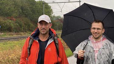 Op deze foto zijn de twee horecaondernemers te zien, ze wandelen door de regen.