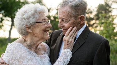 foto van echtpaar dat na 60 jaar in dezelfde trouwkleding poseert