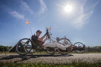 Een foto van een rolstoeler tijdens de vierdaagse van Twente, in de volle zon