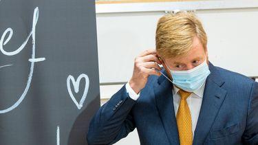 Een foto van koning Willem-Alexander met een mondkapje