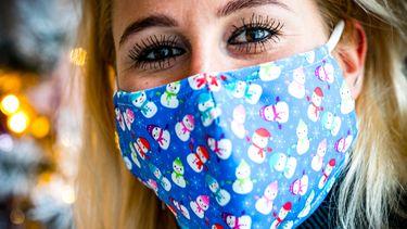 Een foto van een vrouw met een mondkapje met kerstopdruk