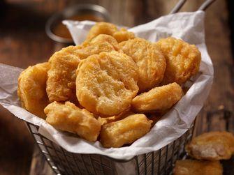 Op deze foto zie je een bakje met kip nuggets