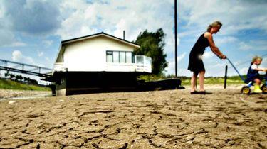 Een foto van extreem droge grond met op de achtergrond een moeder met een kind