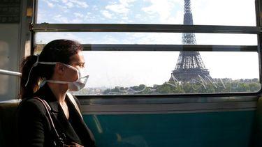 Een foto van een meisje met een mondkapje in het ov, reizend langs de Eifeltoren