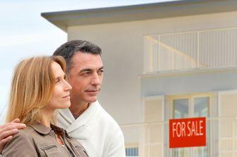 Een foto van een stel voor een huis dat te koop staat