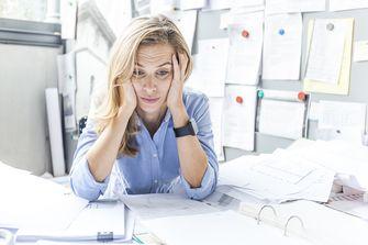 Op deze foto zie je een vrouw met stress aan tafel