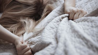 Een vrouw in bed onder de dekens