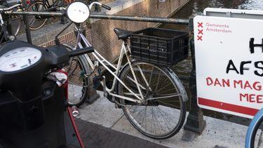 Een foto van een bord met de tekst houd afstand aan een Amsterdamse brug
