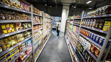 Op deze foto is iemand in een supermarkt te zien, tussen twee schappen.