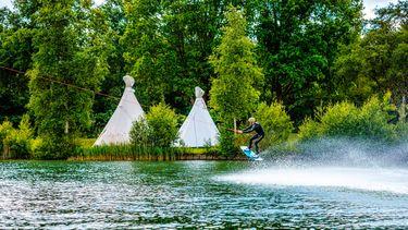Foto van twee tipi-tenten en een watersporter